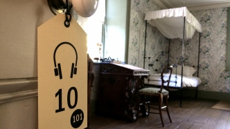cardboard luggage tag with number 10 hanging on door knob with period period in background