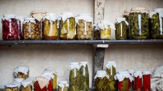 Rows of jars of pickles on shelves.