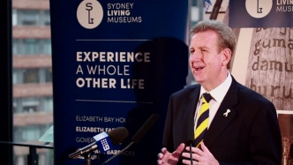 Premier Barry O'Farrell speaking at a lectern in front of a Sydney Living Museums banner.