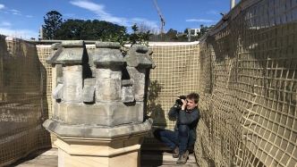 man with large camera photographing stone turret.