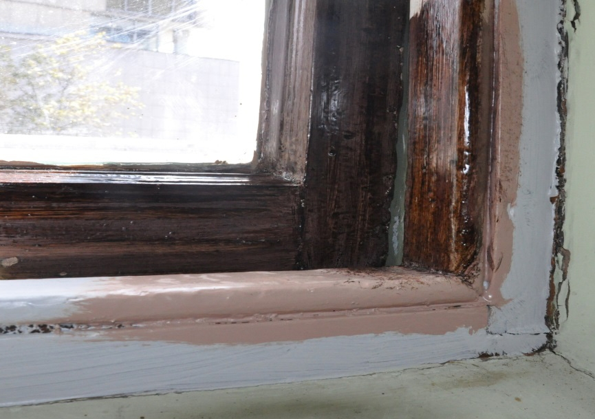 Closeup of corner of window frame showing different layers of paint.