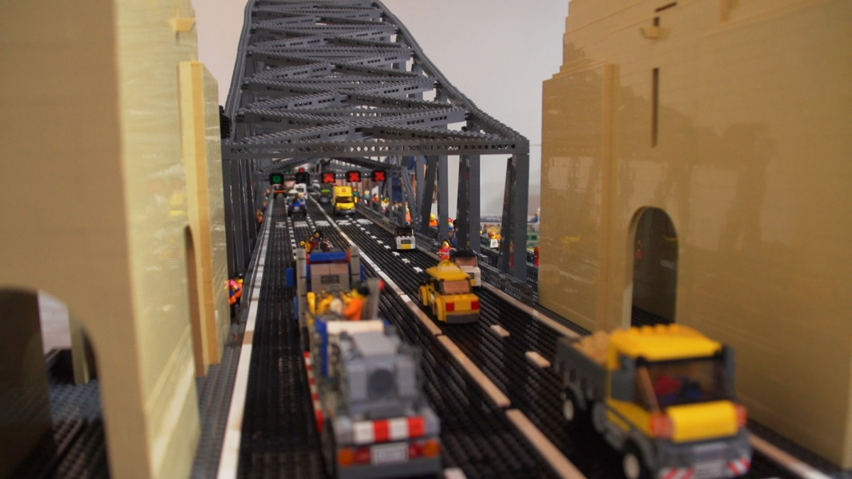 view along the road platform on lego model of sydney harbour bridge showing brown pylons, girders, traffic signals and cars