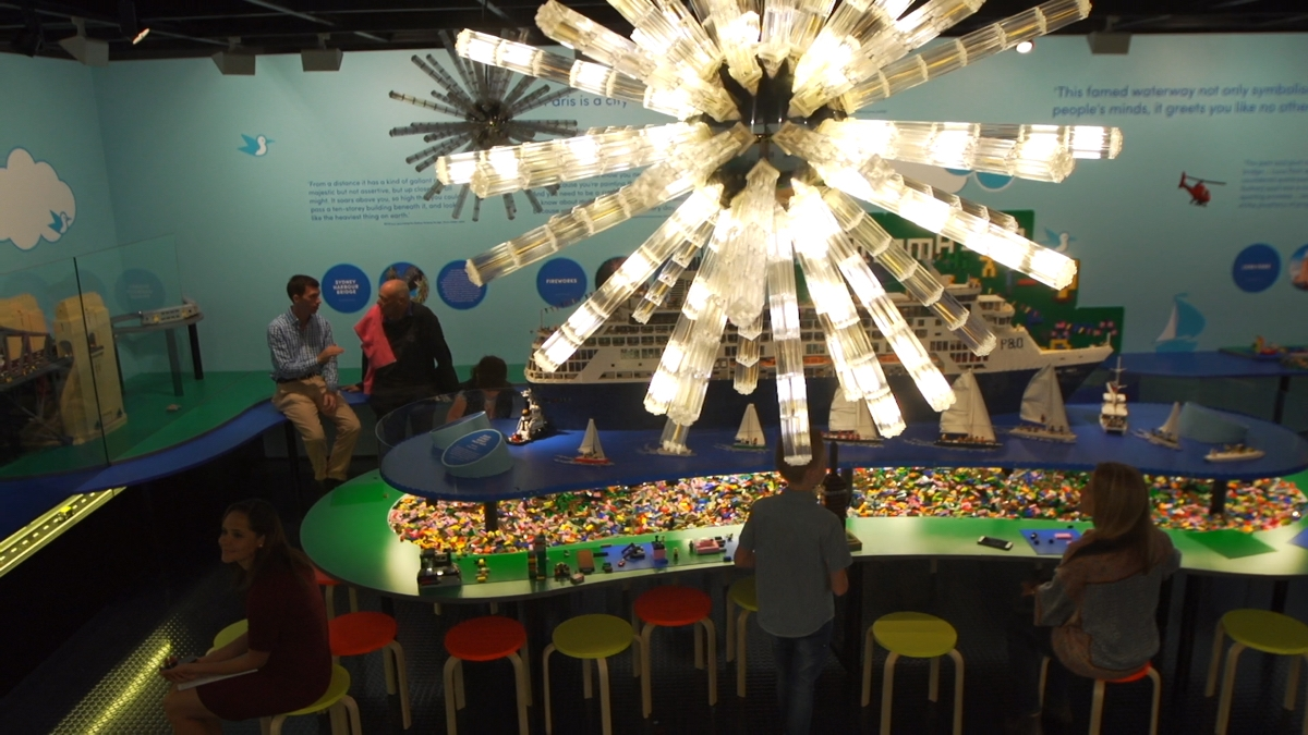 Installtion view of brightly lit Lego fireworks model hovering over exhibition of Lego Models