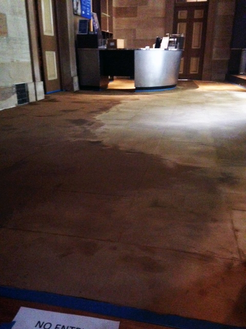 Floor showing wear, with desk area in background.