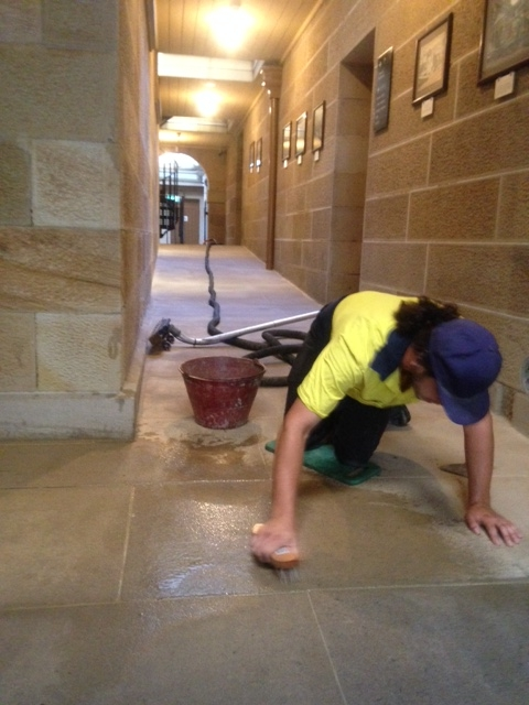 Man in bright yellow and blue work shirt scrubbing floor.