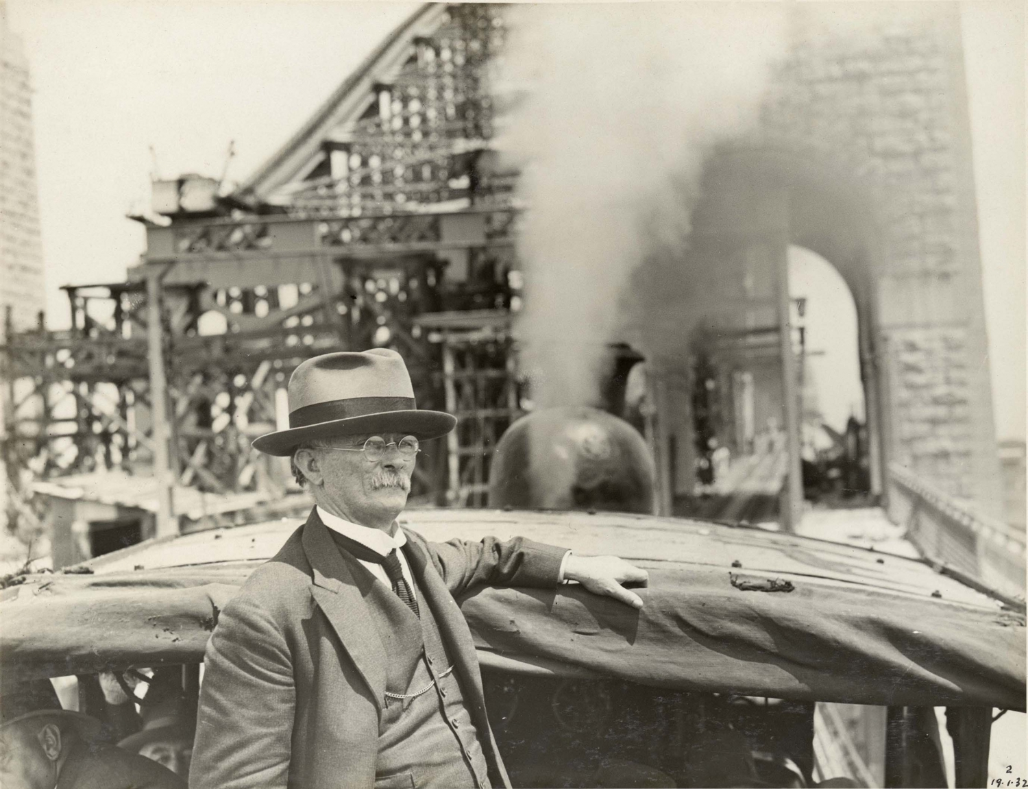 Photograph of a man with white hair and large moustache standing beside a car, construction of the bridge is in full swing in the background.