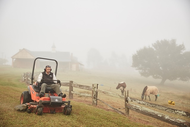 Photograph of a gardener mowing the lawns at Rouse Hill House & Farm