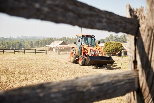 Photograph of a tractor mowing the paddocks at Rouse Hill House & Farm