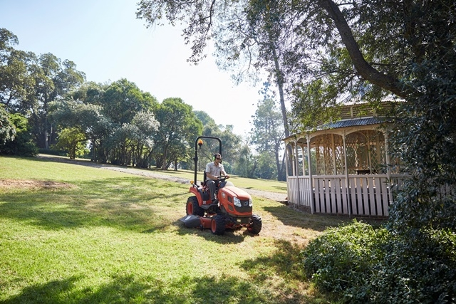 Photograph of a horticulturist mowing the grass at Rouse Hill House & Farm