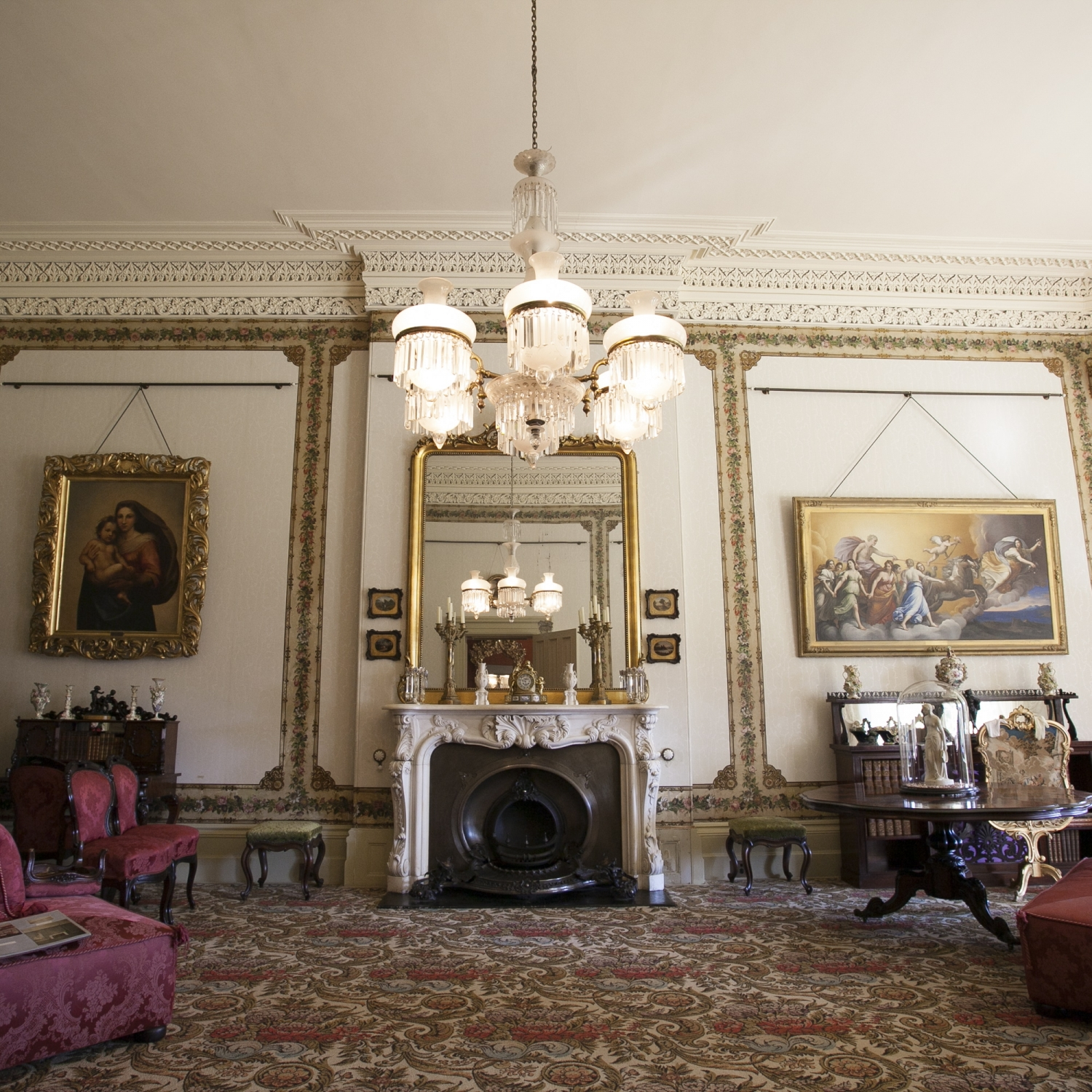 Drawing room with furniture and chandelier, reflecting in mirror above fireplace.