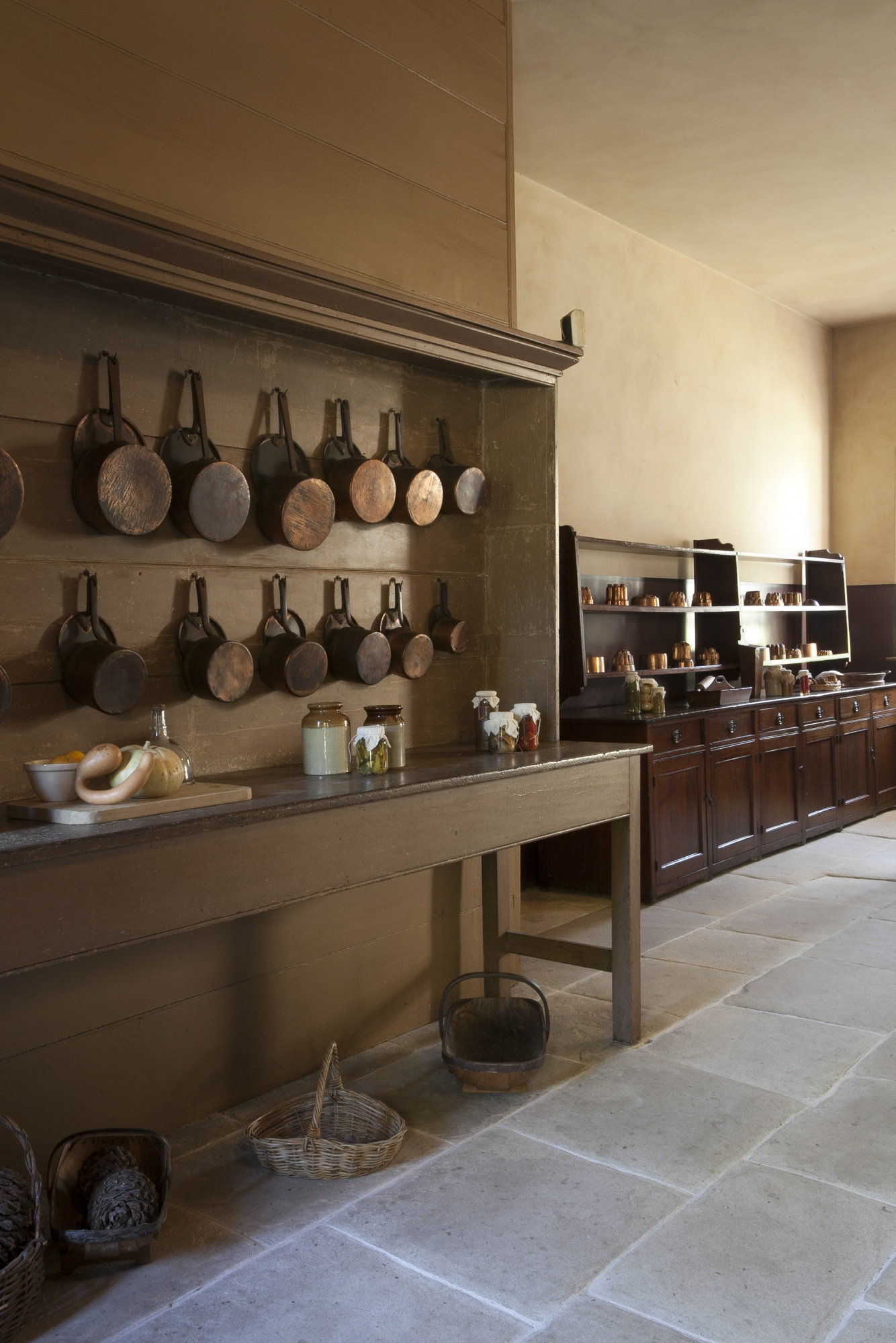Two wooden dressers; one in foreground with series of hanging copper pots, one in background with copper jelly moulds.