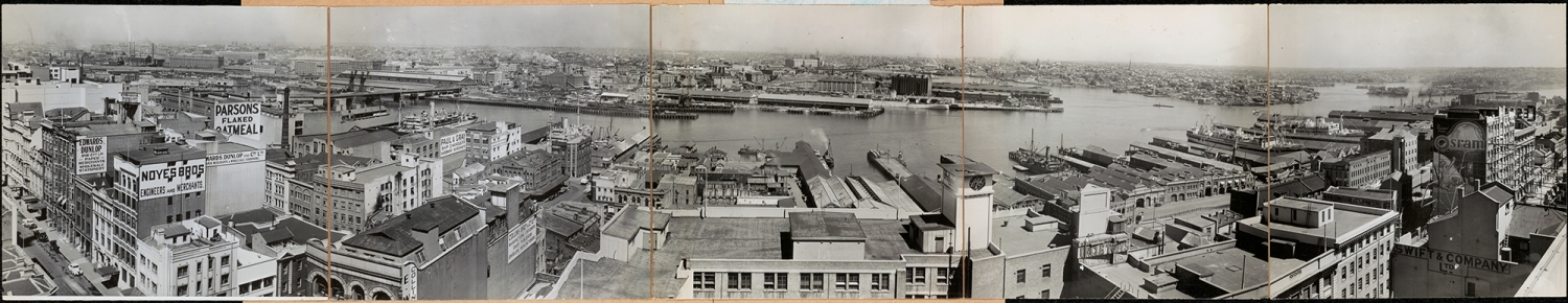 Black and white panoramic view across buildings and water.
