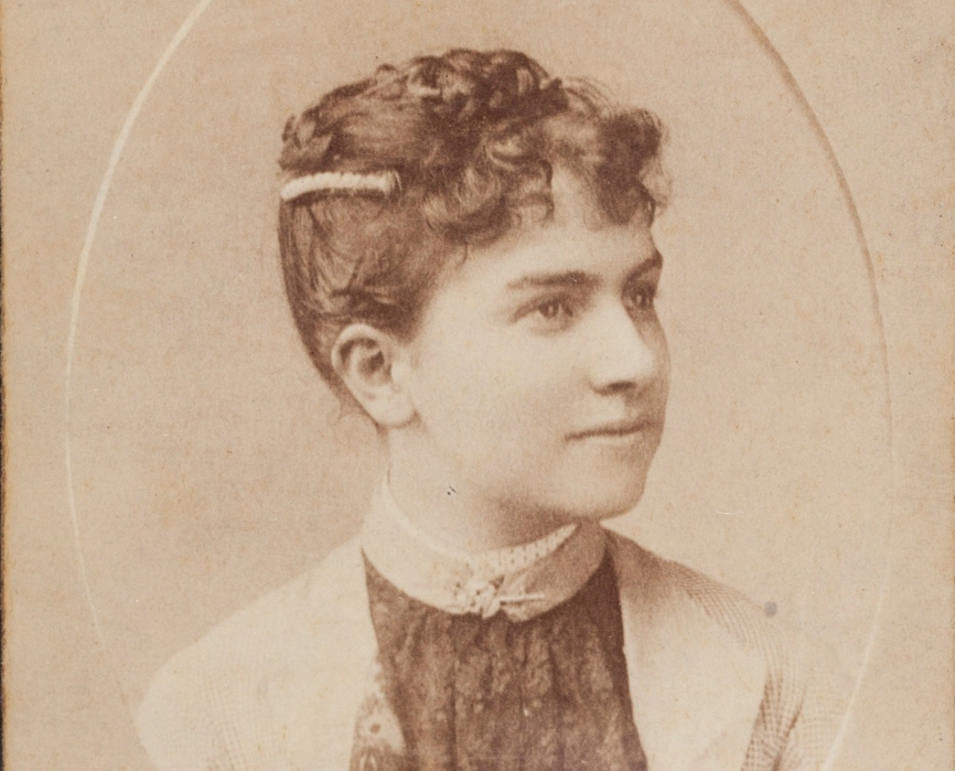 Sepia-toned photograph of dark-haired woman with light-coloured coat over dark top.