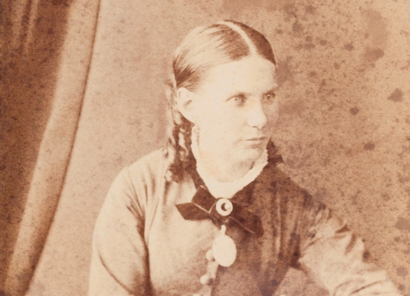 Formal portrait of young lady with plaited hairstyle.