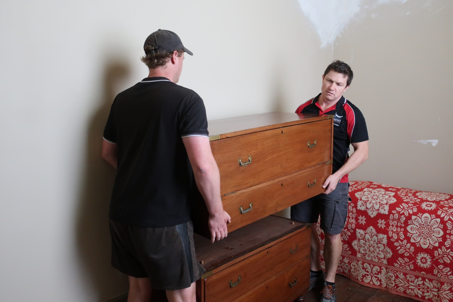Two men carrying wooden furniture.