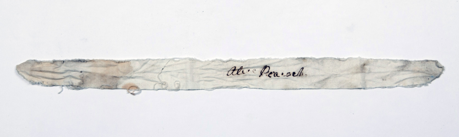 Stained strip of fabric with 'Alice Peacock' written on in a cursive style.
