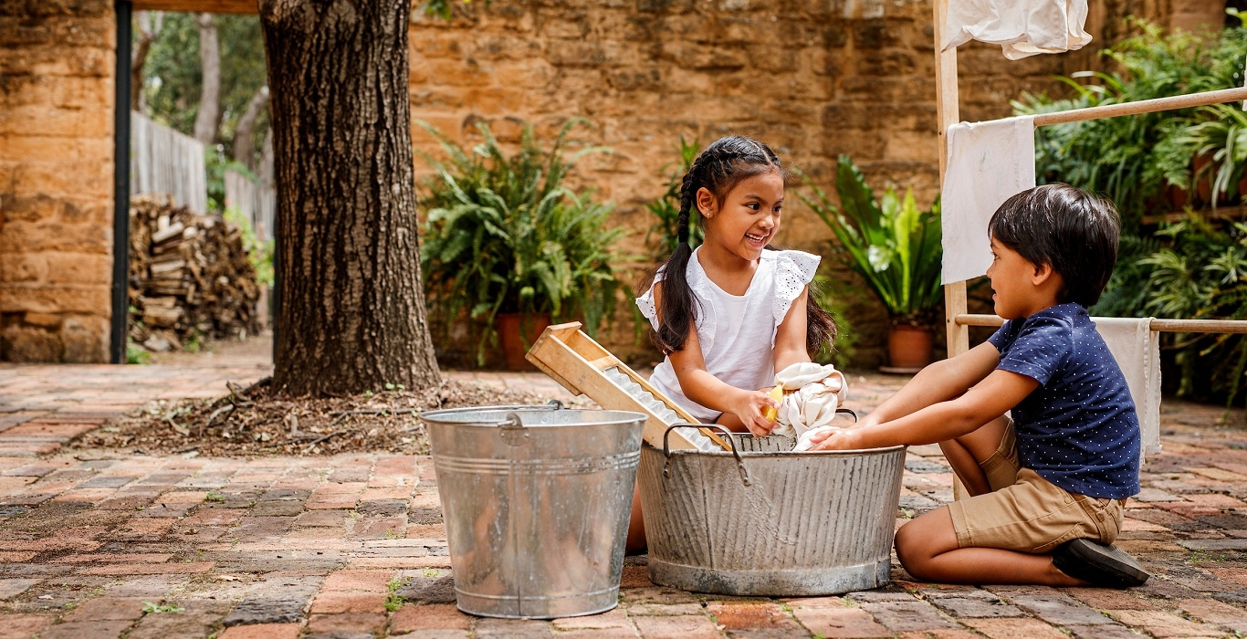 Girl and boy washing clothes in tub