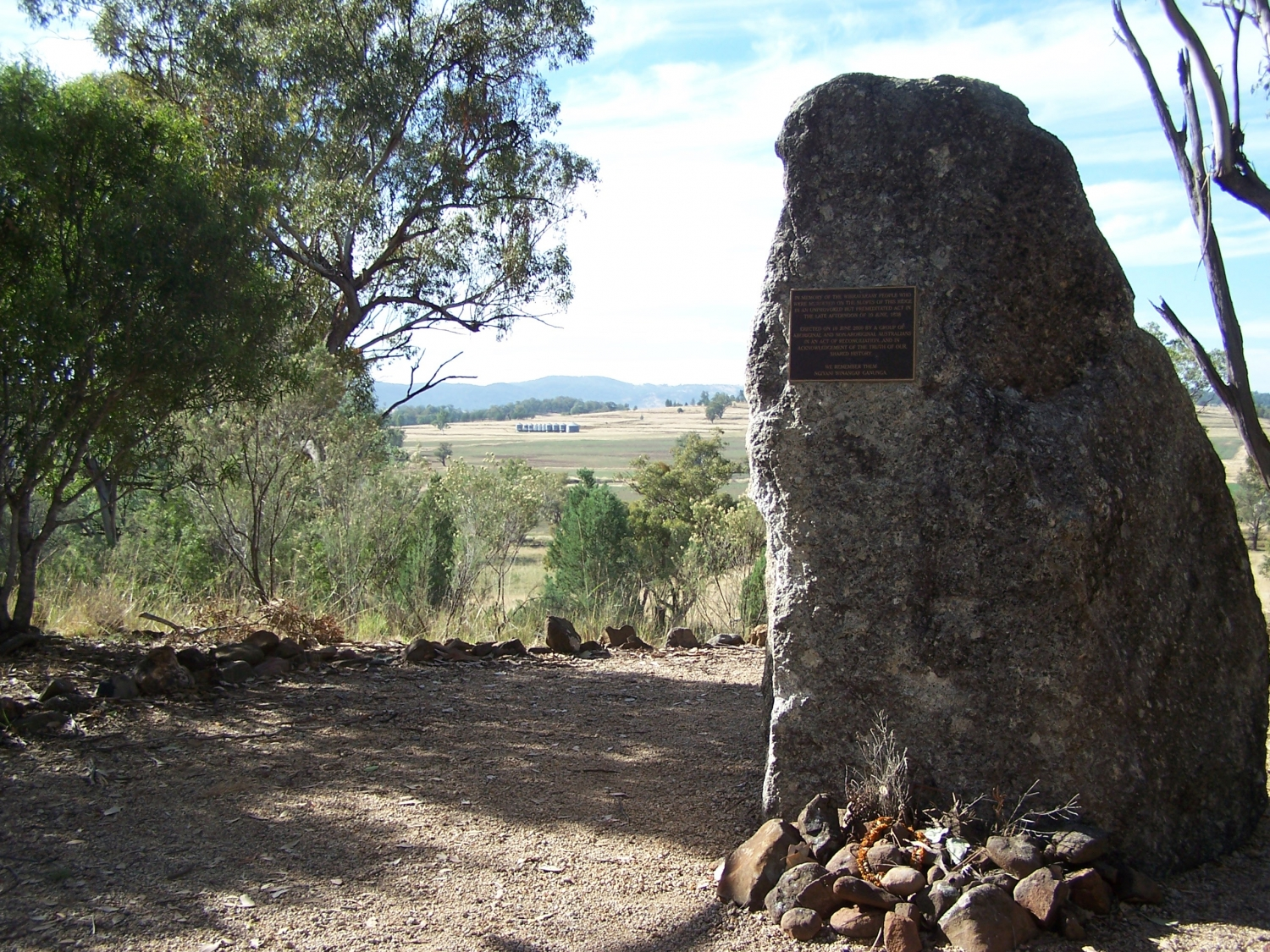 Memorial stone with view of country in background.