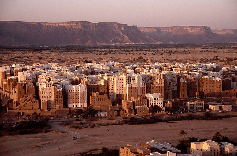 Image of city in desert setting with mountains in background.