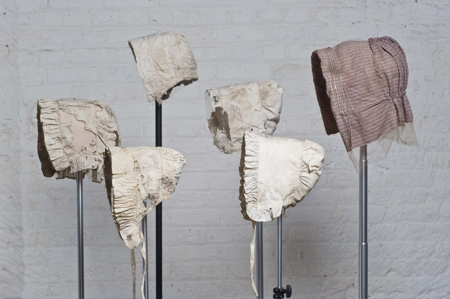 A collection cotton bonnets, displayed on stainless steel stands, photographed against a lime-white painted brick wall.