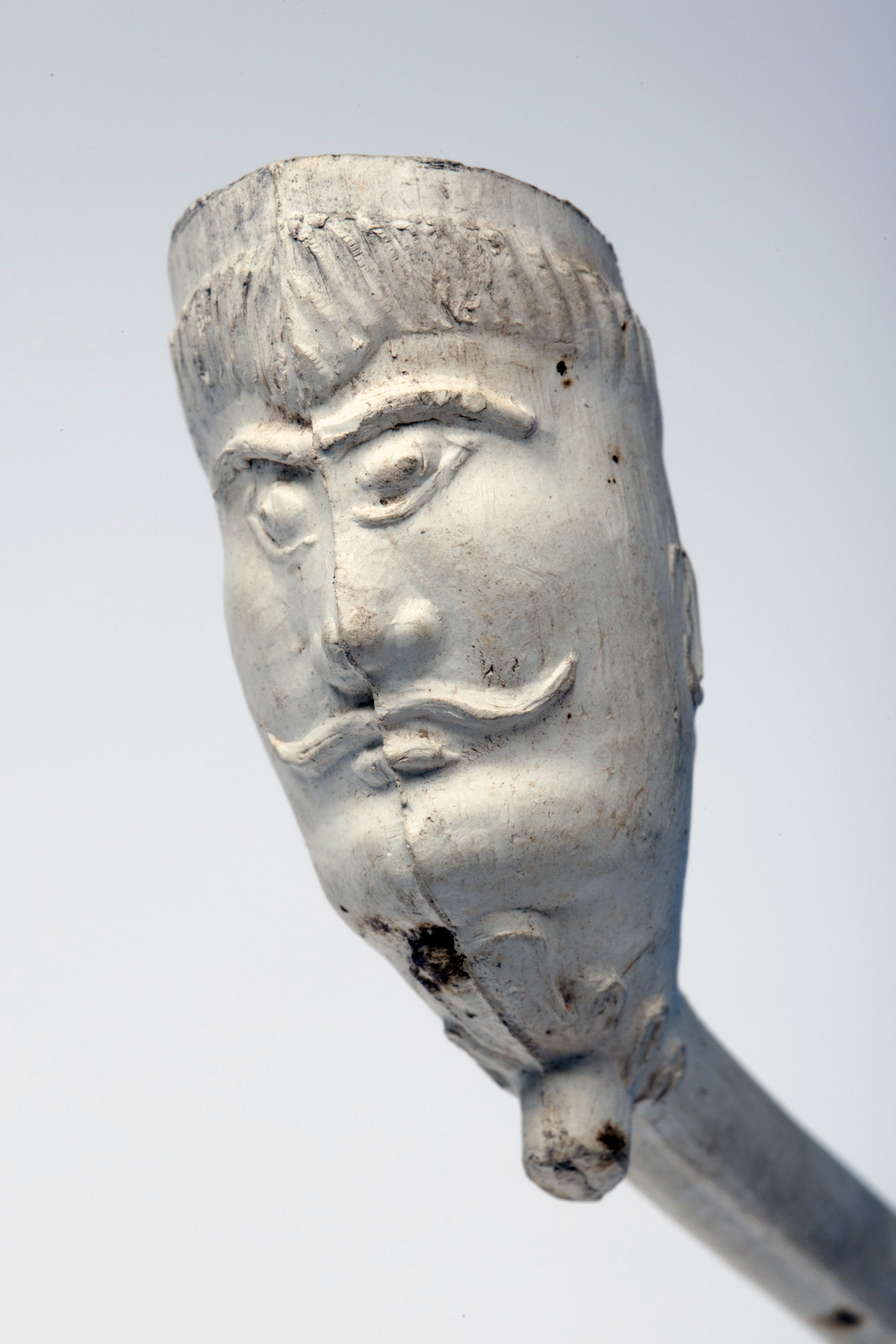 Front view of face carved onto white clay pipe bowl. Face has prominent eyebrows and moustache.