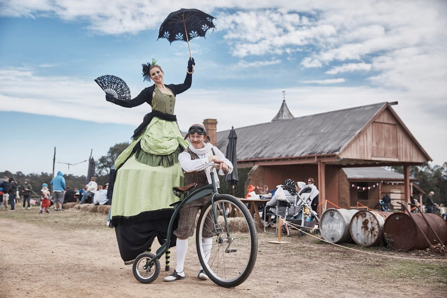 Woman and man in costume with an old fashioned bike