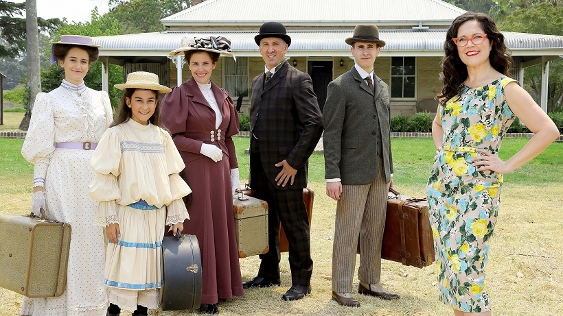 Family dressed in period clothes with woman wearing modern clothes standing in front of colonial style home