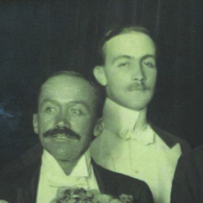 Close up detail of larger group photo showing two men, one in front with moustache.