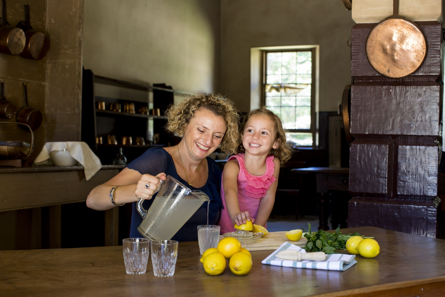 Woman and child seated at large wooden table with makings of lemonade; the woman is pouring lemonade out of a jug.