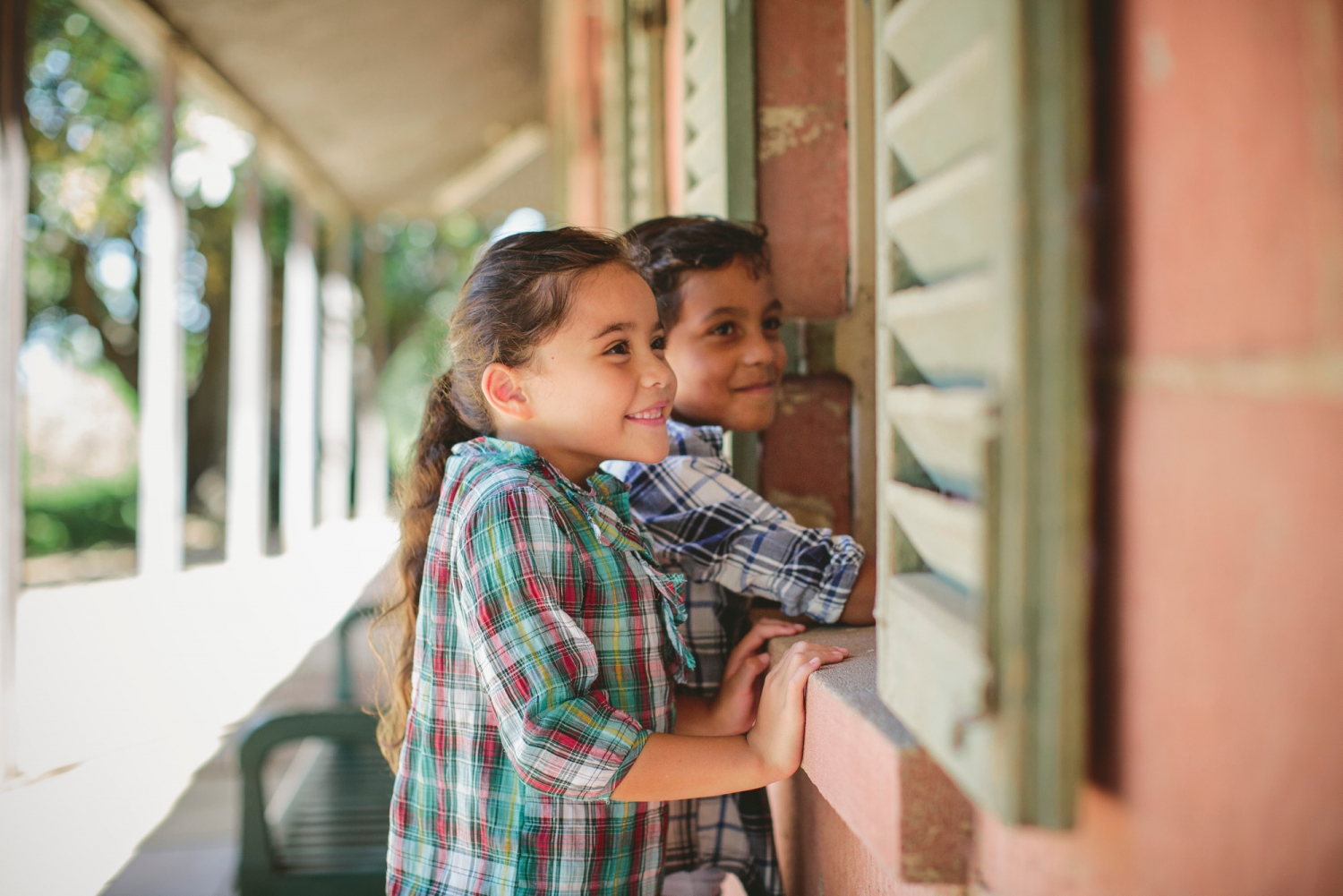 Two children looking through green-shuttered window.