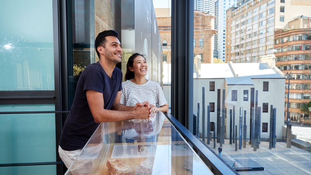 Man and woman standing in glass-walled space with view of street below.