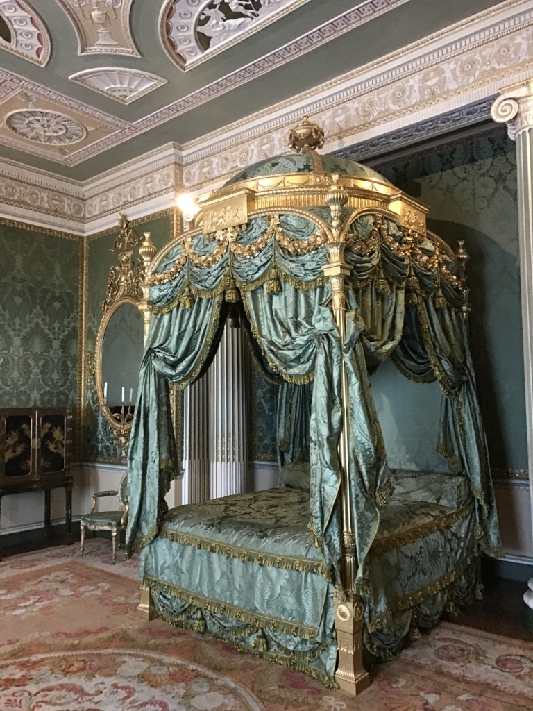 Ornately draped four poster bed.
