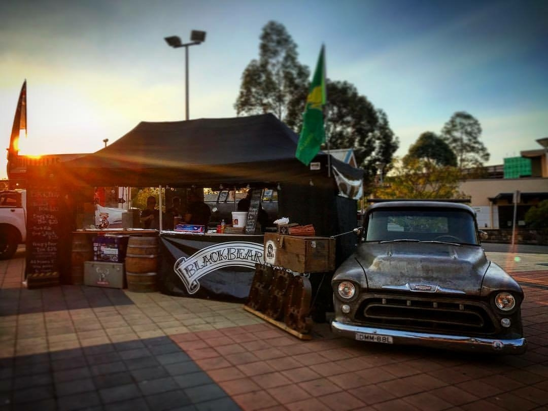 Outdoor market food stall with vintage car.