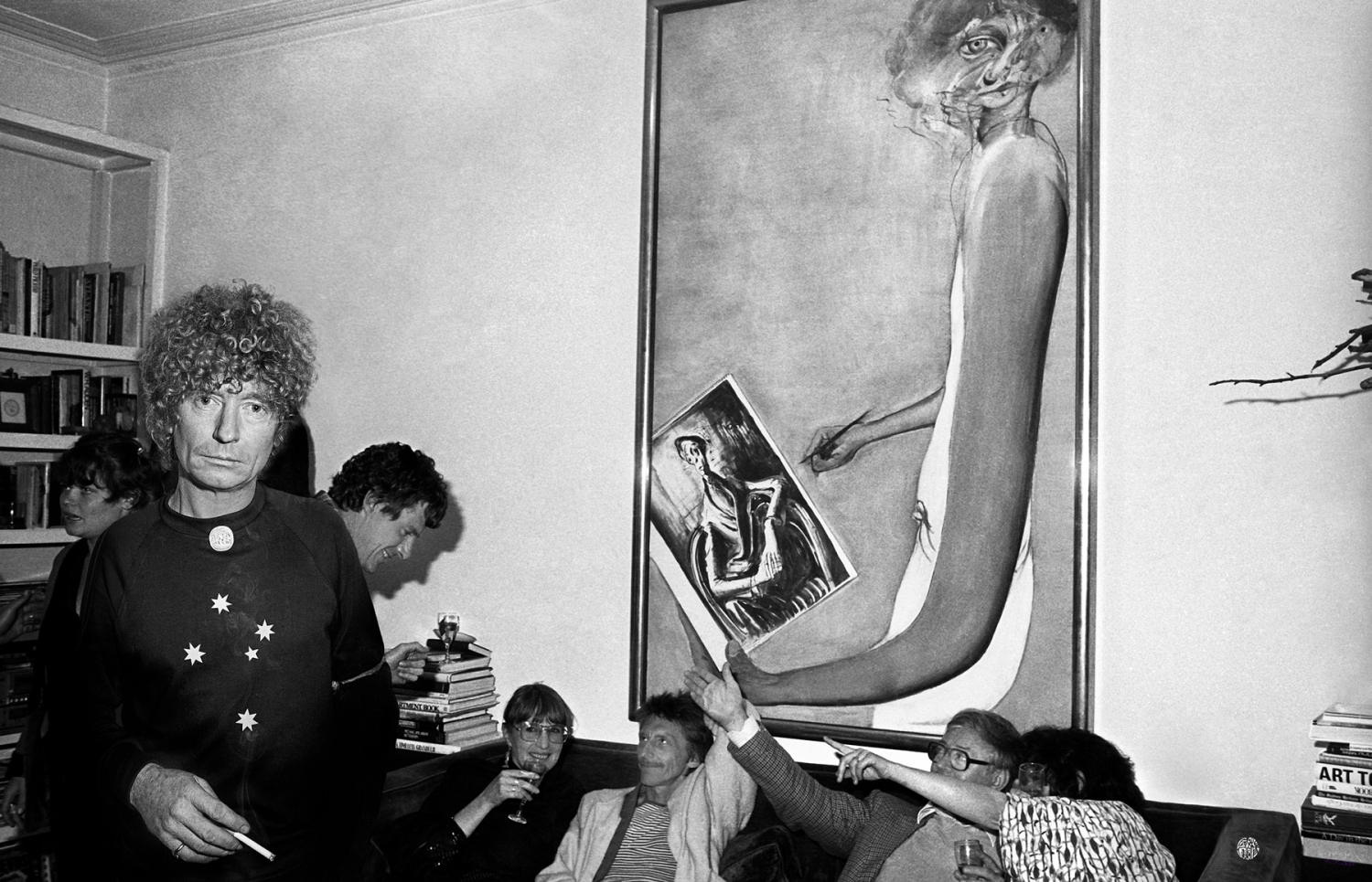 Group on couch with large artwork on wall, behind Brett Whiteley, who is standing looking at camera.