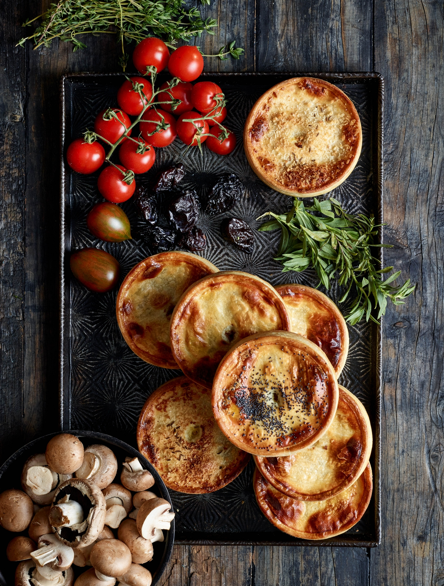 Rectangular food platter with selection of pies and fresh produce.
