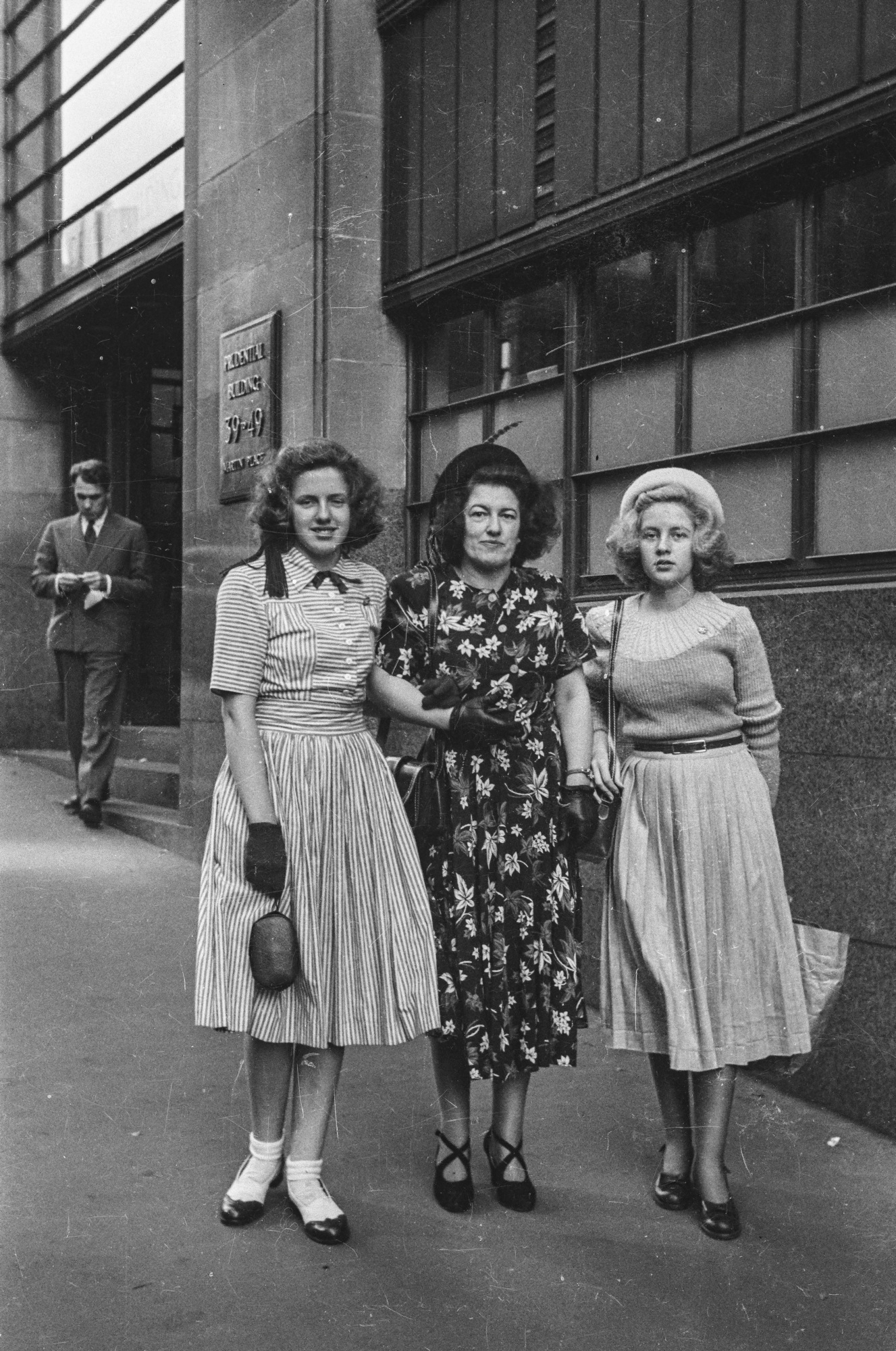 Black and white street photograph of three women linking arms standing in the street.