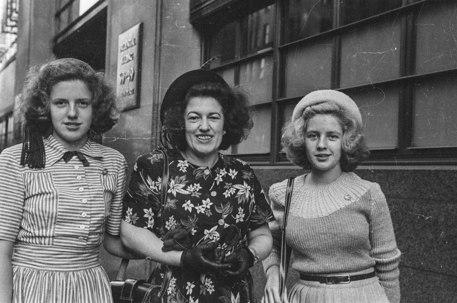 Black and white street photograph of three women linking arms walking down the street.