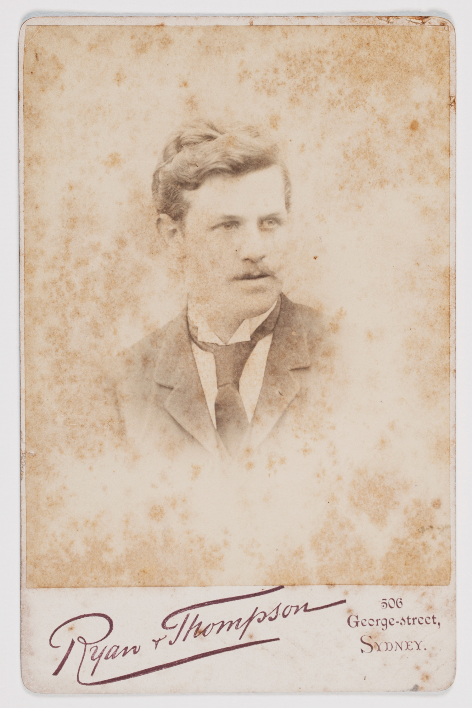 Sepia toned and faded portrait of young man with tie.