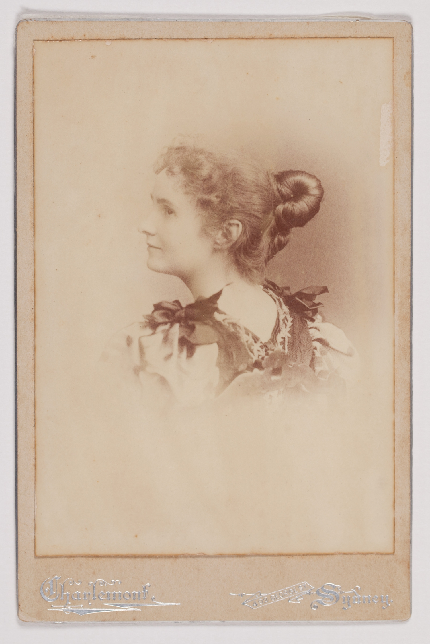 Side view portrait of young woman with hair up in knot.