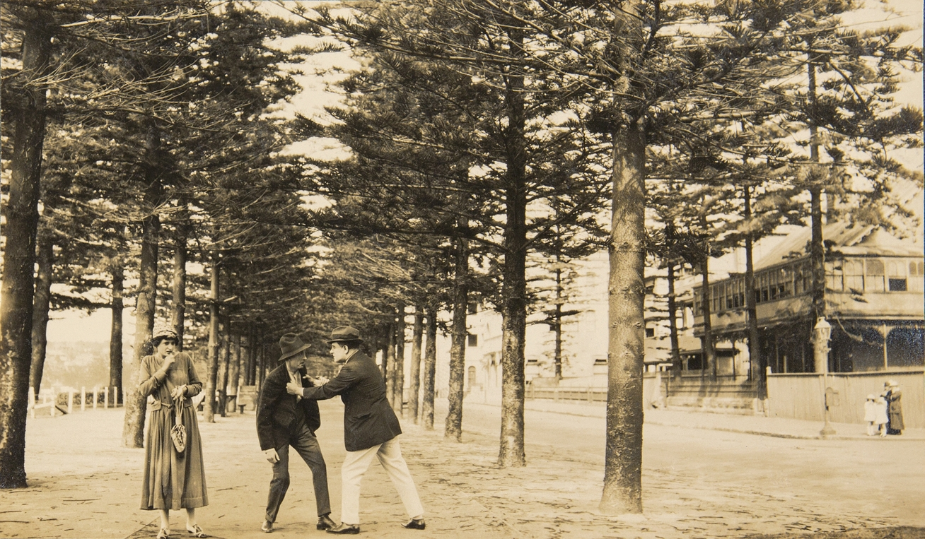 Black and white photo of group on path framed by Norfolk Island pines.