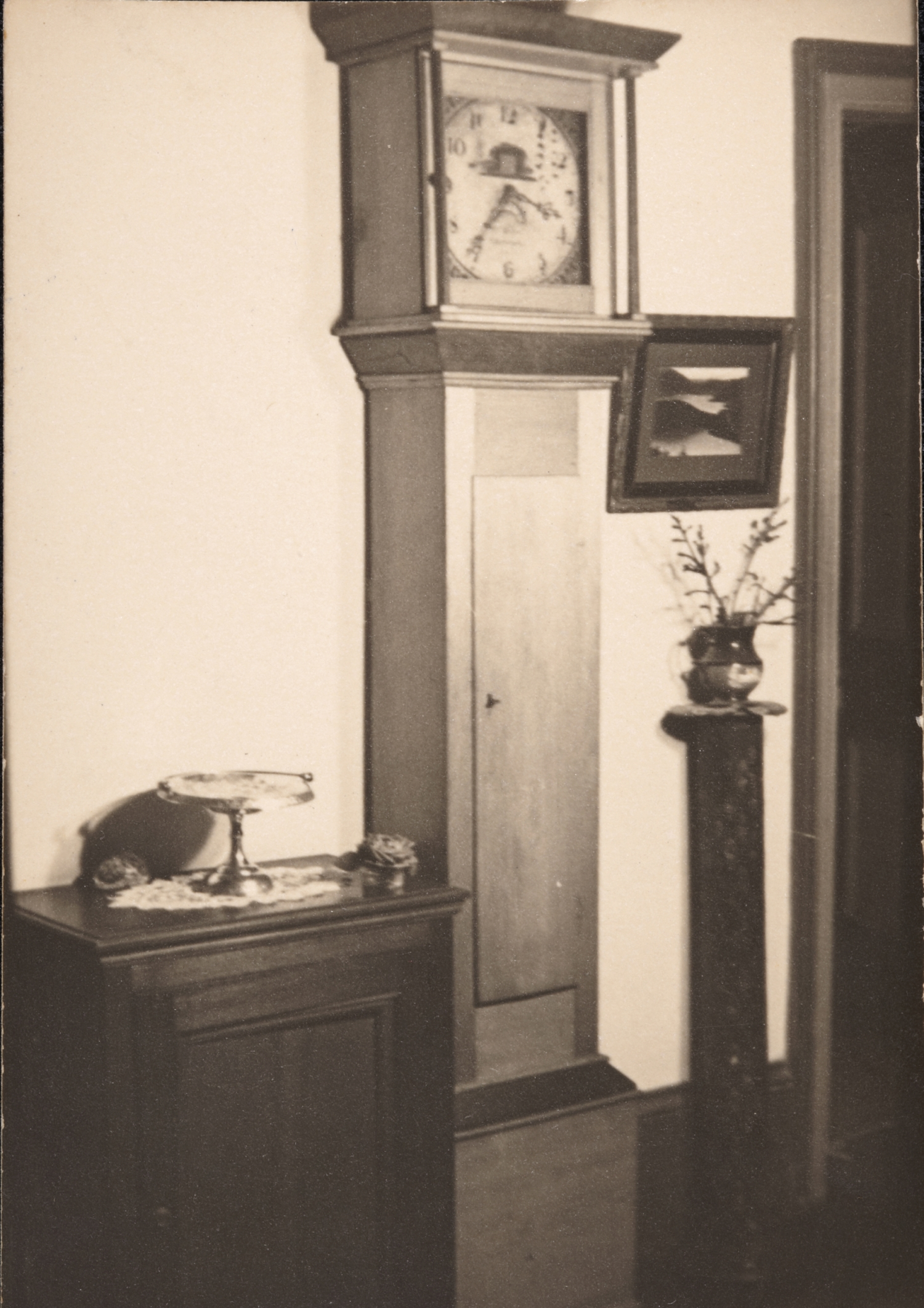 Black and white photo of tall clock in hallway.
