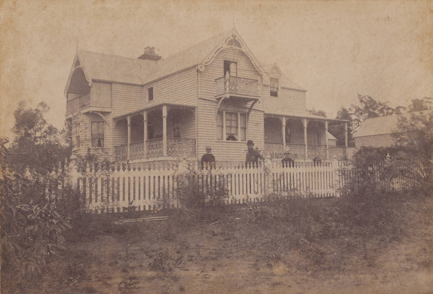 Three people standing behind picket fence in front of two storey house.