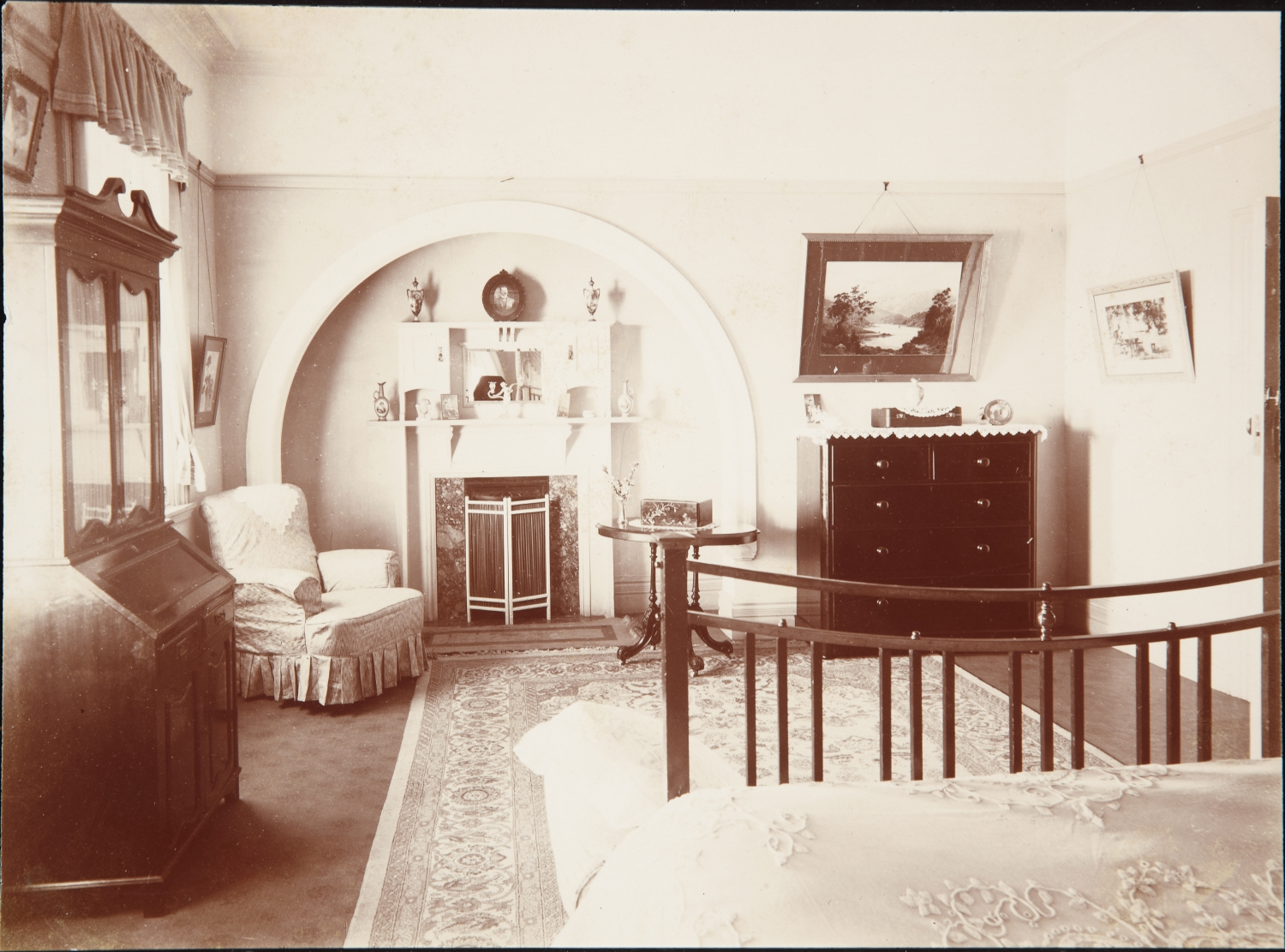 Sepia toned photo of large room with foot of bed visible and fireplace at far end of room.