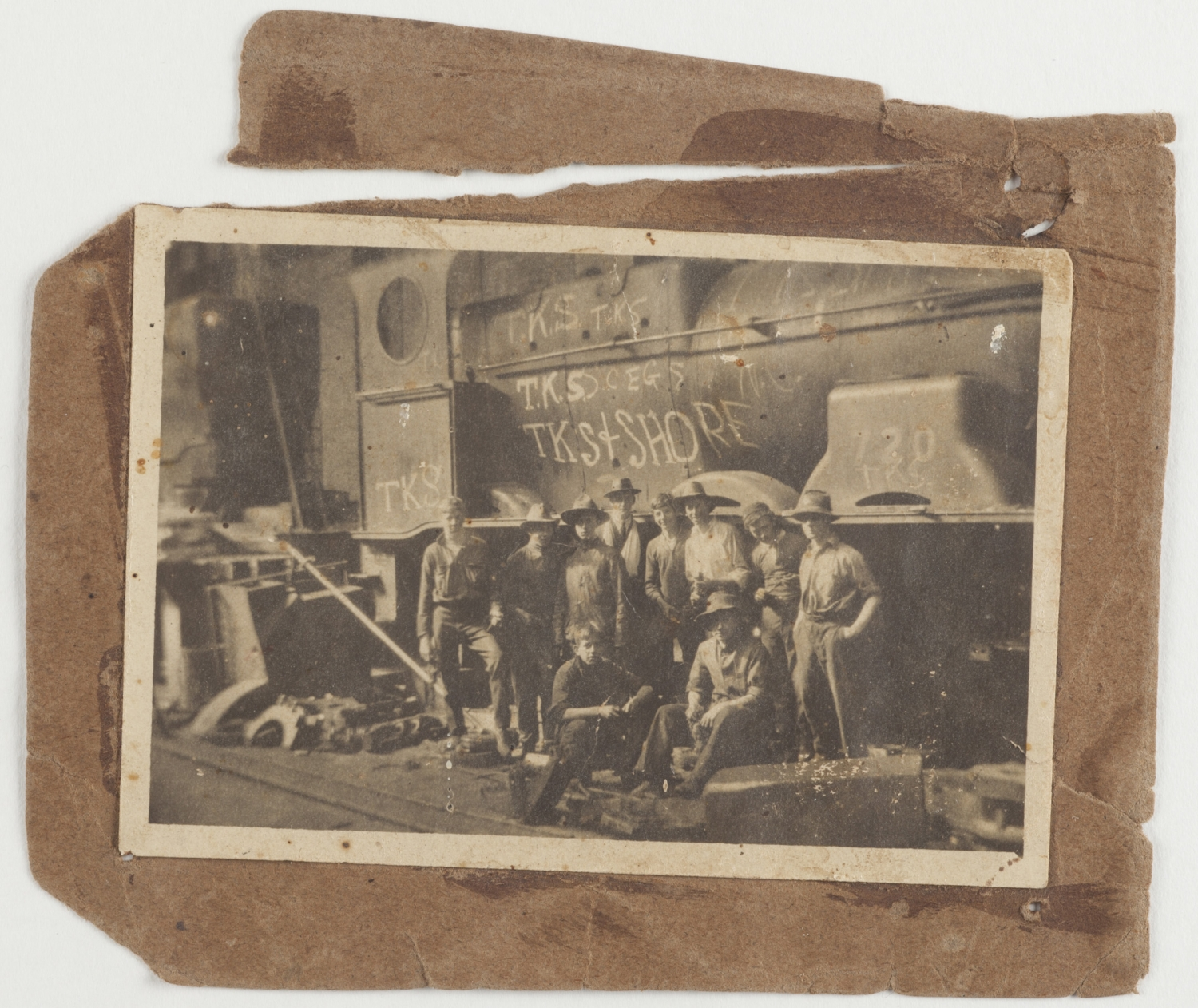 Old photo pasted onto brown card, of group of boys in front of train engine.