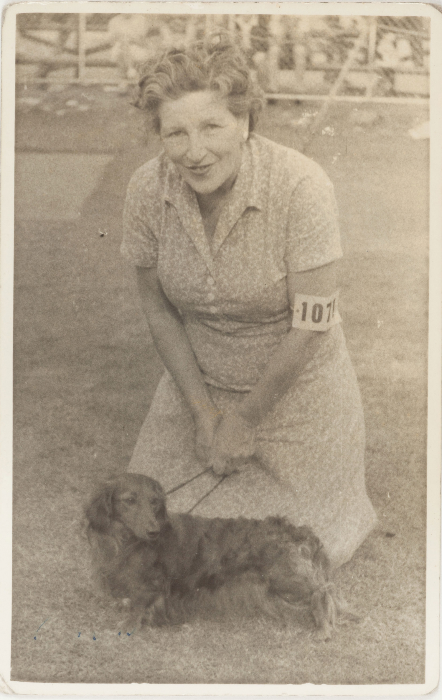 Woman kneeling on grass with daschund on lead in front of her.