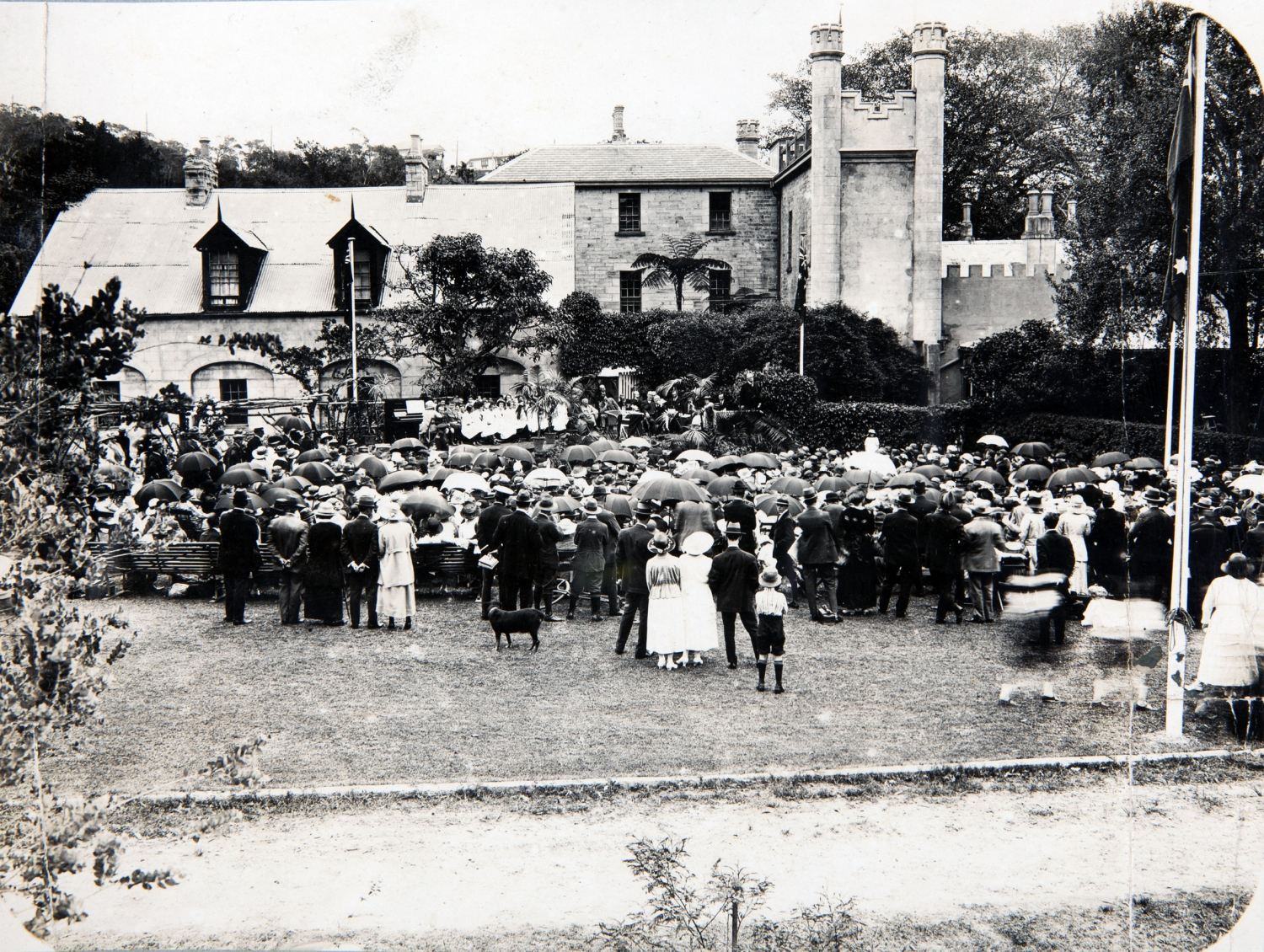 Black and and white photo of crowds on lawn at side of house, with flag pole visible to right.