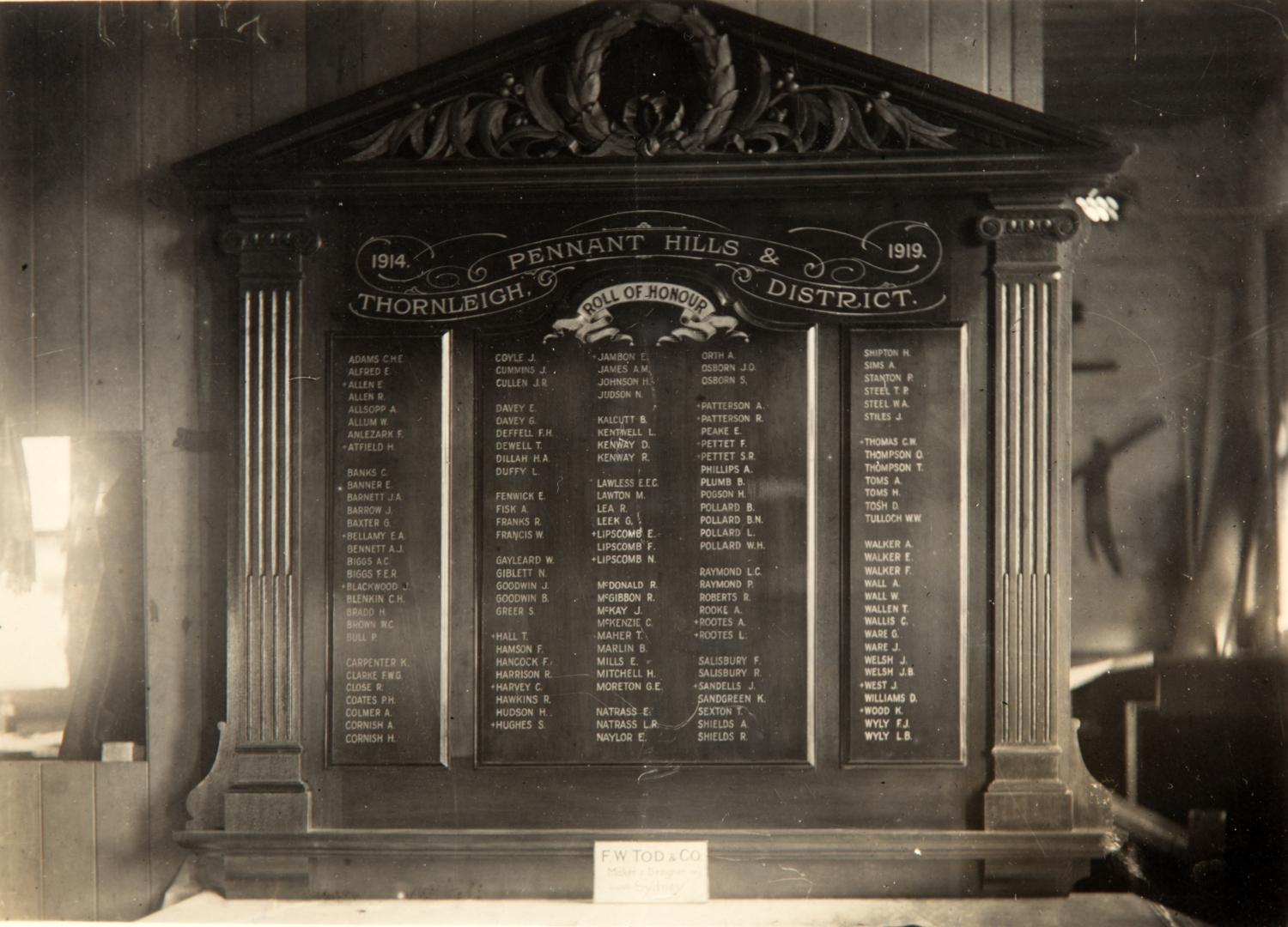 Aged black and white photo of honour roll in situ with window to left.