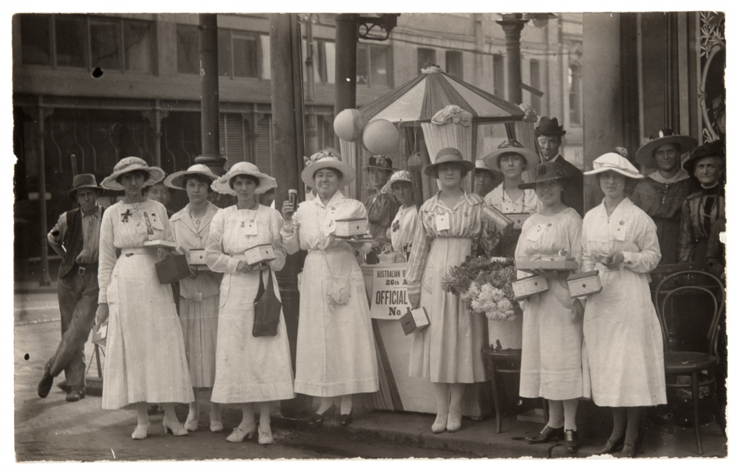 Women in white in front of stall.