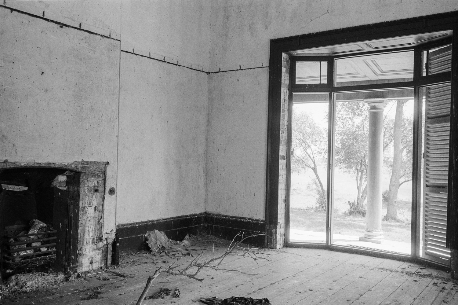 Interior of neglected room with branches on floor near fireplace and window.