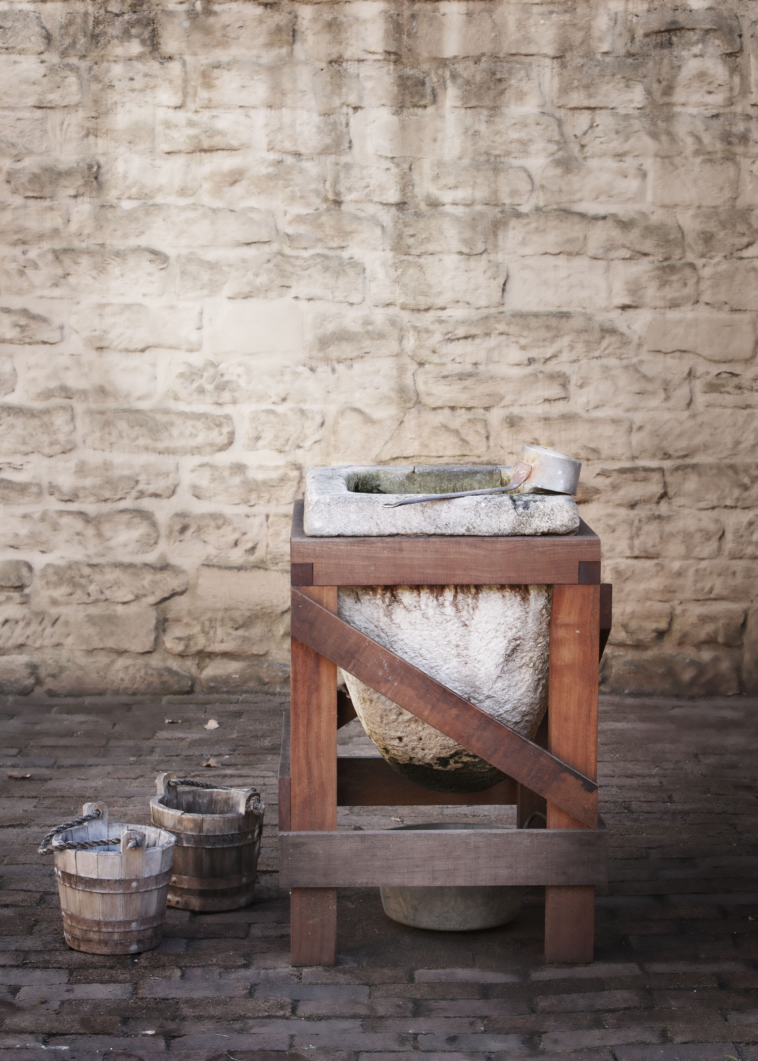 dished out stone water filter resting in timber frame or cradle against a stone wall